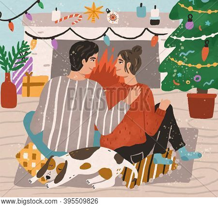 Young Couple Hugging And Sitting On Carpet By Fireplace At Home Decorated With Xmas Tree And Other C
