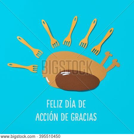 paper cutouts in the shape of a roast turkey and some forks, and the text happy thanksgiving day written in spanish on a blue background