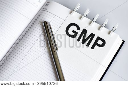 Text Gmp On Short Note Texture Background With Pen