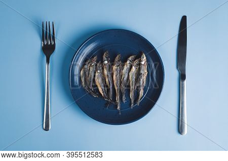 Dried Smelt Fishes On Plate With Fork And Knife, High Angle View, Blue Background. Concept Of Diet O
