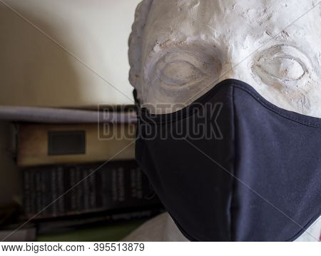 Incomplete Male Bust Wearing Black Face Mask With Boo-ks Background. Arts At Pandemic Times Concept