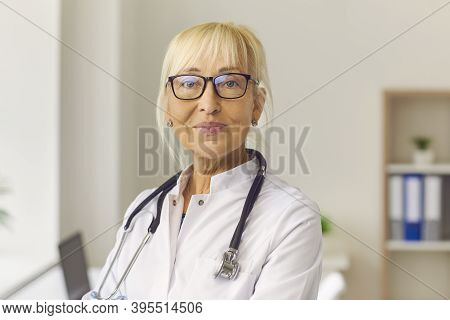 Close Up Portrait Of An Experienced Friendly Senior Doctor Woman Looking At Camera.