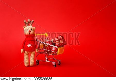 Christmas Presents Or Greeting Card Concept. Amigurumi Deer With A Supermarket Trolley With Christma