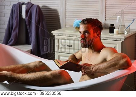 Guy Reading In Bathroom With Toiletries And Chair On Background