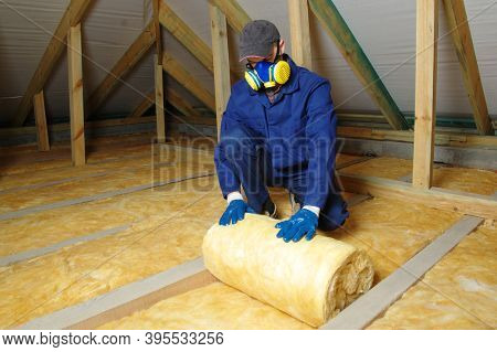 Man installing thermal insulation layer under the roof, using mineral glass wool