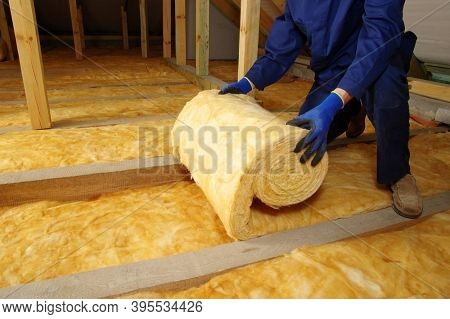 Worker insulate the attic with mineral wool