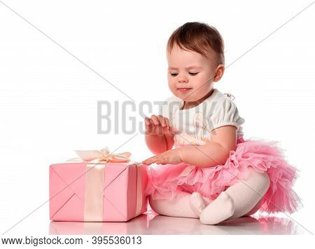 Mistrustful Shy Cute Baby Girl Sitting On White Floor Background And Looking At Gift Box Studio Shot