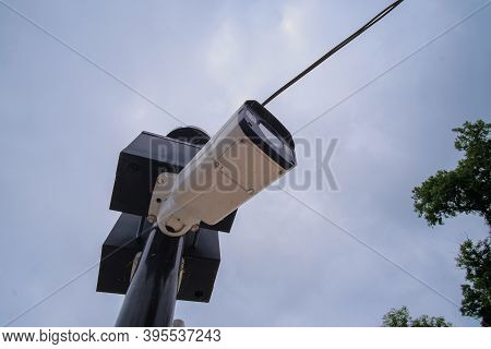 Close Up View Of Security Camera Hanging Among Wire In Guarded City Bridge With Cloudy Sky Backgroun