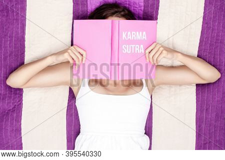 Woman reading purple Karma Sutra book outdoors
