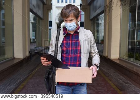 Portrait Of A Young Man In A Medical, Protective Mask, With A Box Of Things, Who Has Lost His Job. T