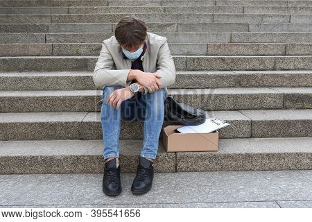Unemployment And Layoffs Concept. Fired A Company Employee Sitting On The Stairs And Suffering From