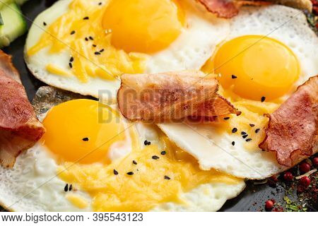 Breakfast Plate With Fried Eggs And Bacon. Macro Photo Of Three Fried Eggs Served With Black Sesame