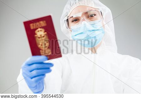 Medical Healthcare Worker In Full Personal Protective Equipment Holding Red Passport,coronavirus Cov