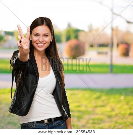 Beautiful Woman Giving Victory Sign, outdoor