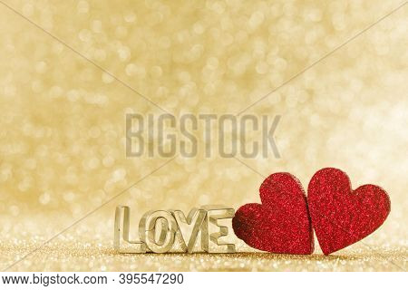 Two red handmade glitter hearts and word love on golden bright glitter lights bokeh background