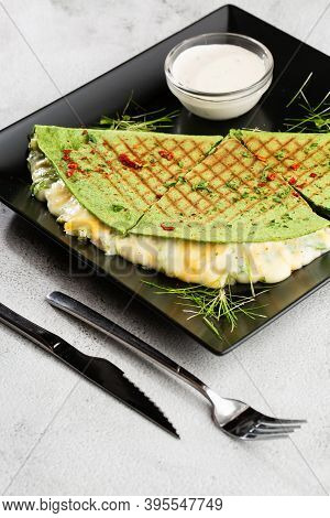 Spinach Green Grilled Crepes With A Cheesy Filling Served With A Sour Cream Sauce And On A Black Pla