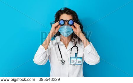 Doctor In Face Mask On Bright Color Background Looking Through Binoculars. Girl In Concept Protectio
