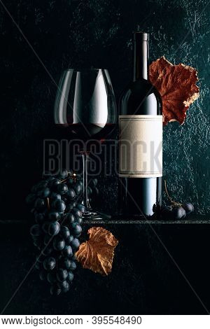 Red Wine And Blue Grapes With Dried Up Vine Leaves On An Old Dark Blue Background. On A Bottle Old E