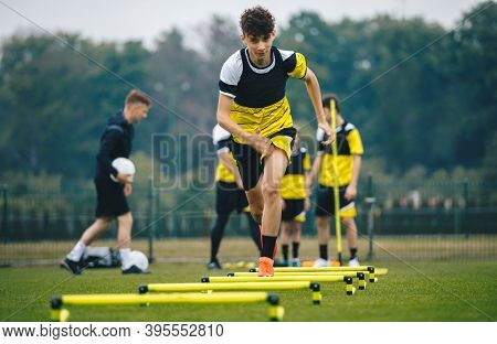 Soccer Training On Hurdles. Group Of Young Boys In Sports Football Club Practicing On Jumping Hurdle