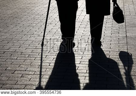 Silhouettes And Shadows Of Two Old People Walking With Cane And Handbag On The Street. Elderly Coupl