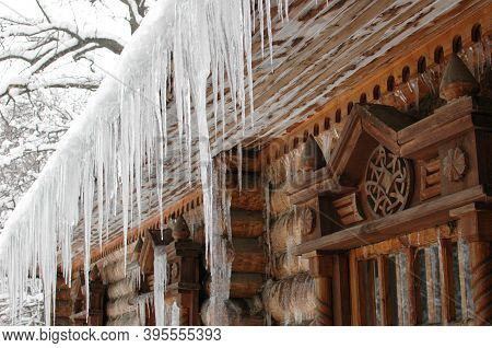Icicles In Winter. The Old Hut Is Covered With Ice In Winter. Icicles Hang From The Roof.