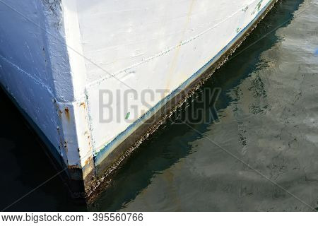 Bow Of White Wooden Boat Sitting On Its Moorings On The Dock.