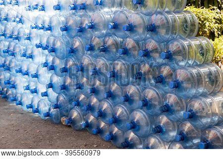 Plastic Water Bottle Background, Blue Bottle Caps, Orderly Arrangement. Empty Bottles For Drinking W