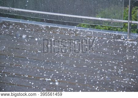 Tiny White Grains Of Hail And Rainwater Cover The Brown Tiled Balcony. Detailed Close Up Shot Of Rai