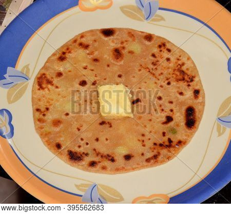Indian Popular Breakfast Spicy Aloo Paratha Served With Butter Cube On Top Of It