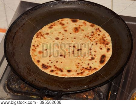 Close Up Of Traditional Indian Aloo Paratha Preparation In Progress On A Round Pan