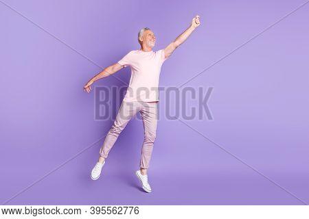 Full Length Profile Photo Of Old Man Tiptoe Raise Hand Look Empty Space Wear Pink T-shirt Pants Snea