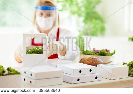 Food Takeaway In Restaurant In Coronavirus Outbreak. Cafe Staff In Face Mask And Shield Cooking Take