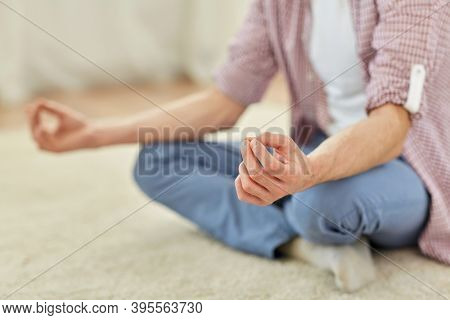 mindfulness, yoga and people concept - close up of man meditating in easy pose at home