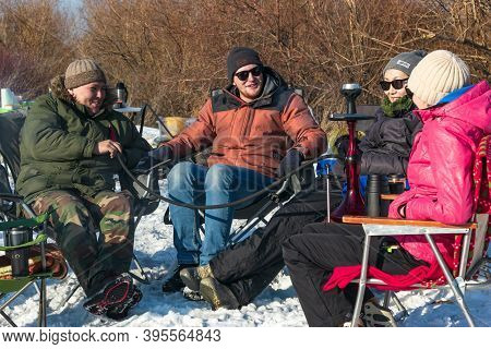 Group Of Friends With Sunglasses Rest On Camping Chairs, Smoking Hookah Outdoors In Campside At Sunn