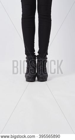 Woman Asian Legs With Black Pant And Heel Is Standing On White Background.