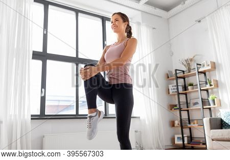 sport, fitness and healthy lifestyle concept - smiling young woman stretching leg at home