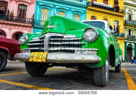 HAVANA-NOVEMBER 28:Old Chevrolet in front of colorful buildings November 28,2012 in Havana.Thousands of these cars are still in use in Cuba and they have become an iconic view of the cuban cities