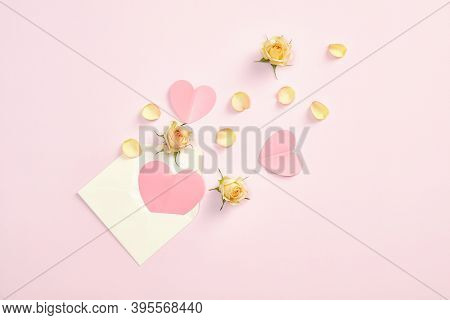 Envelope With Pink Paper Hearts And Roses Flowers Petals And Buds On Pastel Pink Background. Valenti
