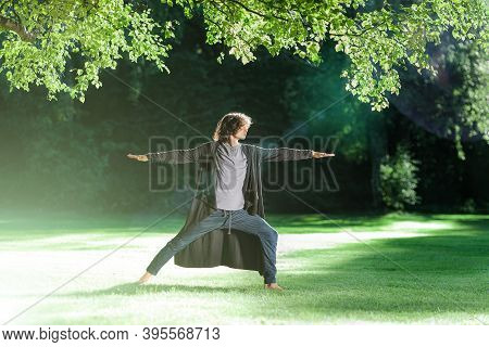 Young Handsome Man Practicing Yoga In The Evening Park Under Oak. Sun Reflections And Flare. Standin