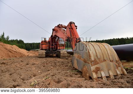 Excavator During Earthwork For Laying Crude Oil And Natural Gas Pipeline In Forest Area. Installatio