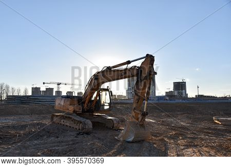 Excavator On Earthworks At Construction Site. Backhoe On Foundation Work And Road Construction. Towe