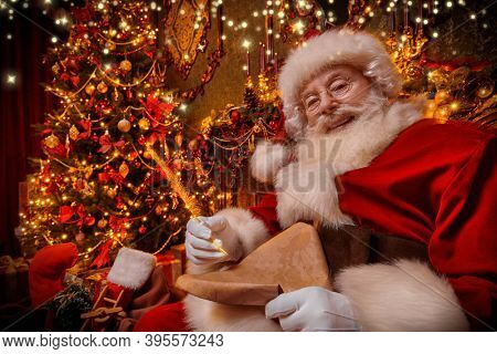 Santa Claus bagging Christmas presents, checking out a list of wishes. He sits in an armchair in a beautiful Christmas interior. Christmas and New Year concept.