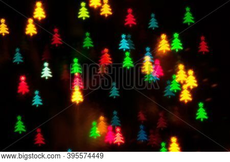 Christmas festive background. Christmas blurred wallpaer. Blurred Christmas background, festive multicolor bokeh Christmas wallpaper. Holiday Christmas glowing color lights with Christmas tree