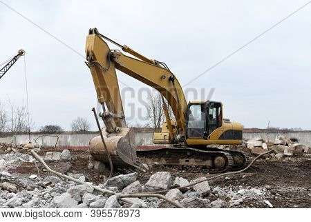 Excavator With Bucket At Demolition Of Tall Building. Hydraulic Machine For Demolish. Backhoe Destro