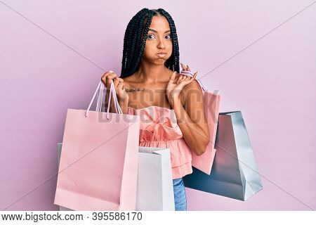 Beautiful hispanic woman holding shopping bags puffing cheeks with funny face. mouth inflated with air, catching air.