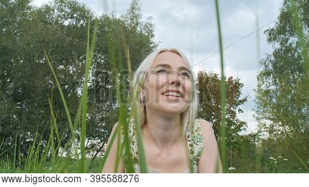 A Young Smiling Beautiful Woman In A Light Dress Lies On The Grass And Looks At The Sky Against The