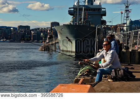Oslo, Norway - Aug. 29th 2020: Anglers Fishing In The Harbor By Moored Warships And Submarine.