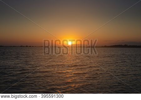 A Colorful Sunset Over A Bay Or Lake With A Calm Water Surface. Late Evening. Low Key
