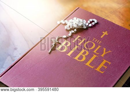 A Rosary Of White Beads With A Silver Crucifix Above The Cover Of The Closed Holy Bible Book. Religi