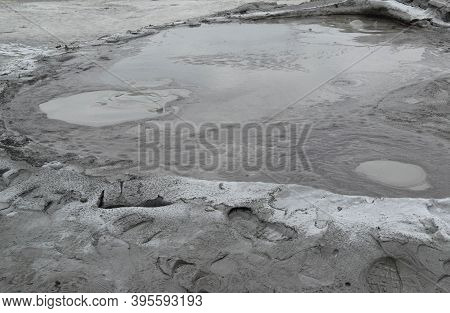 Bubbling Crater Of A Mud Volcano. Close Up View Onto Gas Bubble Exploding In Crater Of Mud Volcano.